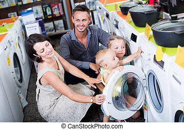Smiling woman and man with kids shopping washer