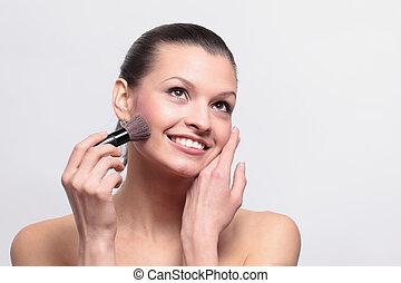 Smiling woman apply makeup