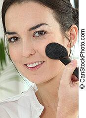 Smiling woman applying blush