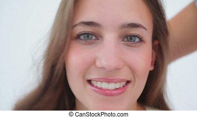 Smiling woman applying make-up