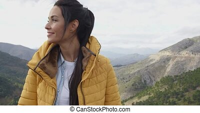 Smiling woman appreciating the peace of nature as she stands...