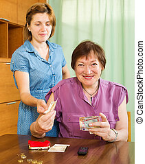 Smiling woman asking aged mother  the money