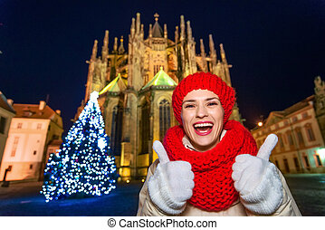 smiling woman at Christmas in Prague showing thumbs up