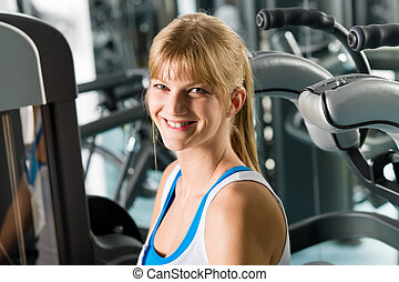 Smiling woman at fitness center exercise machine