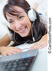 smiling woman at home working on her laptop