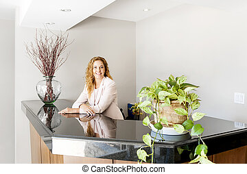 Smiling woman at office reception - Receptionist standing at...