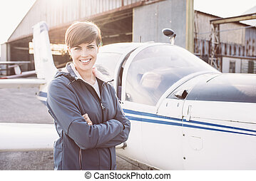 Smiling woman at the airport with light aircraft