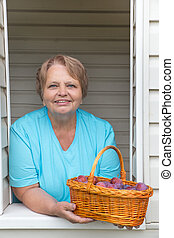 Smiling woman at window shows baske