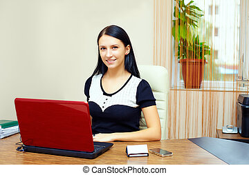 smiling woman at working place in office interior