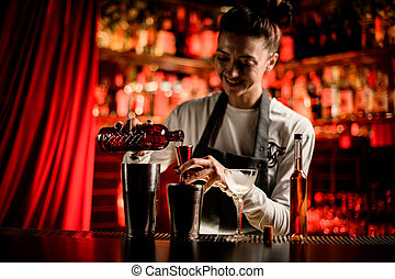 smiling woman bartender holding bottle and pouring drink from it into steel jigger