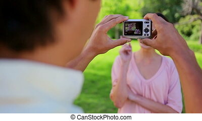 Smiling woman being photographed by her boyfriend
