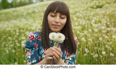 Smiling Woman Blow on a Dandelion