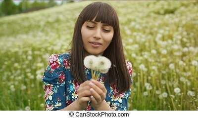Smiling Woman Blow on a Dandelion - Woman blowing dandelion...
