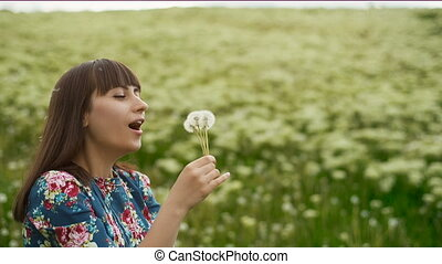 Smiling Woman Blowing on a Dandelion - Woman blowing...