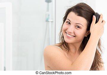 Smiling woman brushing her hair