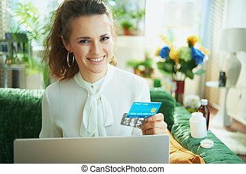 smiling woman buying pharma using laptop