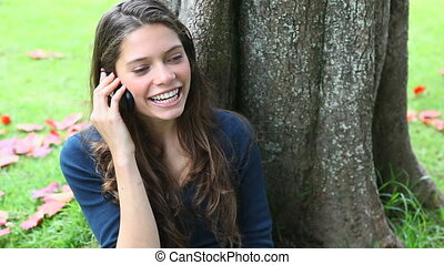 Smiling woman calling in a park