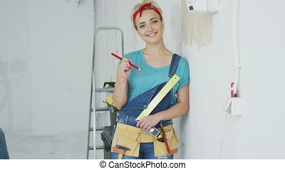 Smiling woman carpenter leaning on wall - Gorgeous young...