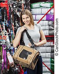 Smiling Woman Carrying Pet Bag In Store