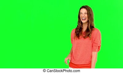 Smiling woman catching a basket ball on green screen in slow...
