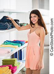 Smiling Woman Choosing Jeans In Store