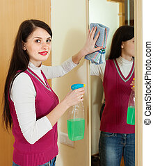 woman cleaning  mirror  with detergent at home