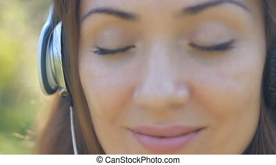 Smiling woman closeup in headphones listening music. Girl smiling and enjoying a song with her eyes closed outdoor