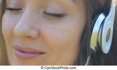 Smiling woman closeup in headphones listening music. Girl...