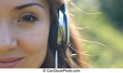 Smiling woman closeup in headphones listening music.