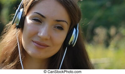 Smiling woman closeup in headphones listening music