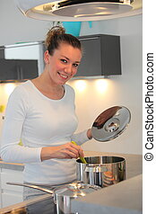 Smiling woman cooking at the stove