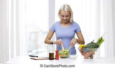 smiling woman cooking vegetable salad at home - healthy...