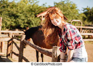 Smiling woman cowgirl sitting on fence in village - young...