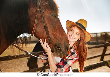 Smiling woman cowgirl standing with her horse on farm -...