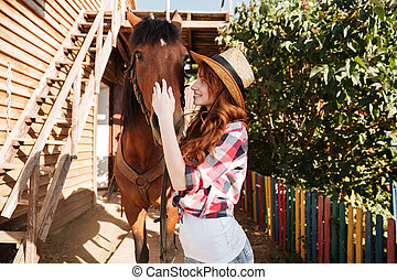 Smiling woman cowgirl taking care of her horse on farm -...