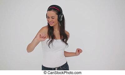 Smiling woman dancing while wearing headphones