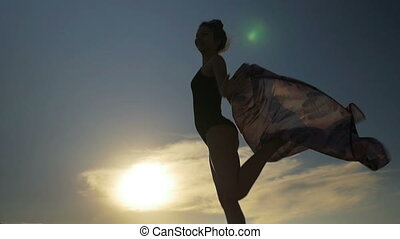 Smiling woman dancing with a scarf in swimming suit in slow...