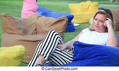 Smiling woman daydreaming and relaxing in the garden -...