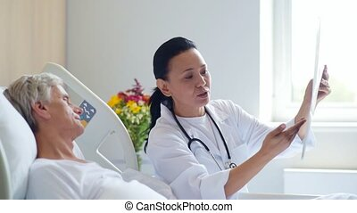 Smiling woman doctor discussing x ray scan with her aged patient