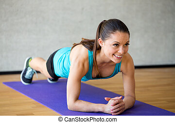 smiling woman doing exercises on mat in gym