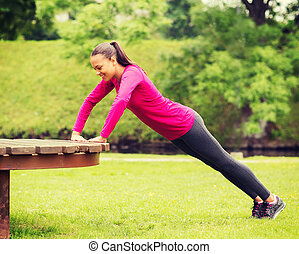 smiling woman doing push-ups on bench outdoors