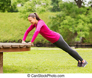 smiling woman doing push-ups on bench outdoors - fitness,...