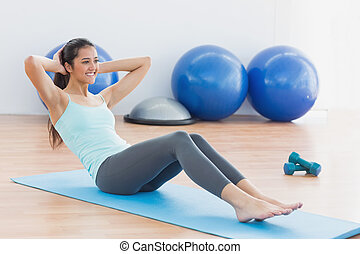 Smiling woman doing sit ups in fitn - Full length of a ...