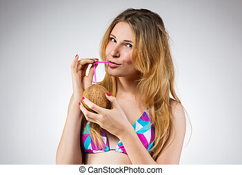 Smiling woman drinking coconut wate