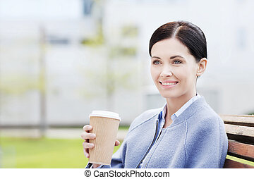 smiling woman drinking coffee outdoors - drinks, leisure and...