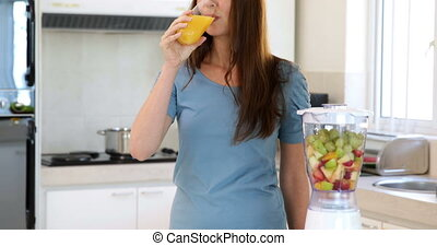 Smiling woman drinking glass of orange juice