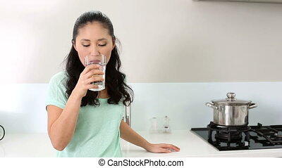 Smiling woman drinking glass of water at home in the kitchen
