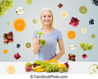 smiling woman drinking juice or shake at home