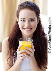 Smiling woman drinking orange juice in bedroom