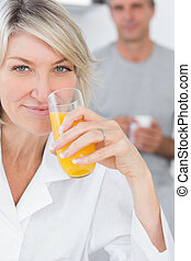Smiling woman drinking orange juice in kitchen